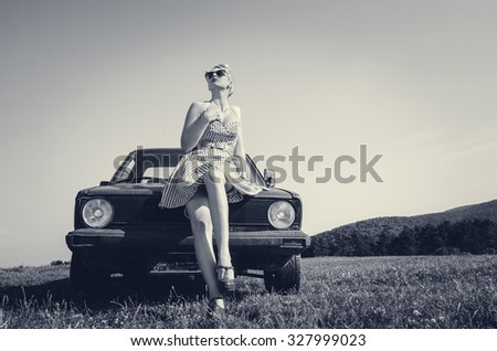 Young attractive female model in short skirt posing and teasing next to retro car. Vintage style.