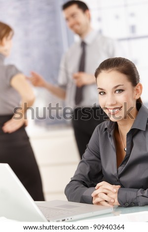 Young attractive female office worker sitting at desk with laptop, smiling, others chatting behind.? - stock photo