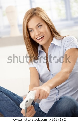 Young attractive female playing video game at home, smiling.?