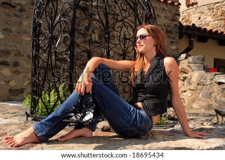 young attractive female posing in front of grate - stock photo