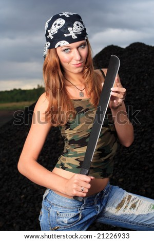 young attractive female posing with sword dressed in camouflage singlet and dark scarf