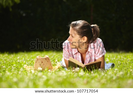 Young attractive female read book in park - stock photo