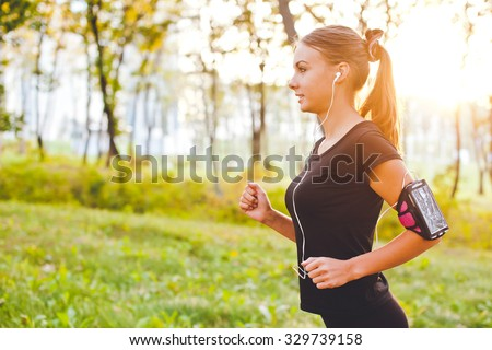 Young attractive female runner with armband running on sunset in park with earphones listening to music during training. Copy space and sun on background - stock photo