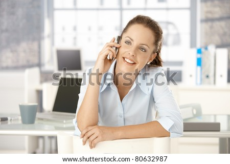 Young attractive female sitting on conversed chair, talking on mobile phone, smiling.? - stock photo