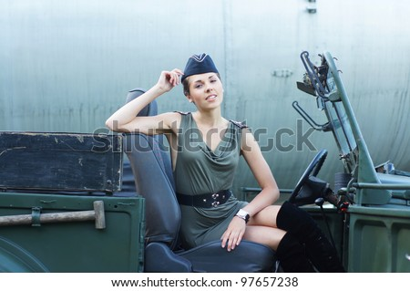 Young attractive female soldier driving the car - stock photo
