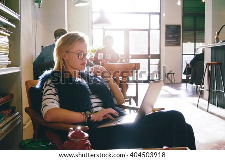 young attractive female student preparing for the exam using laptop while as drinking tea in a cafe. beautiful business woman using a laptop for the distance learning - stock photo