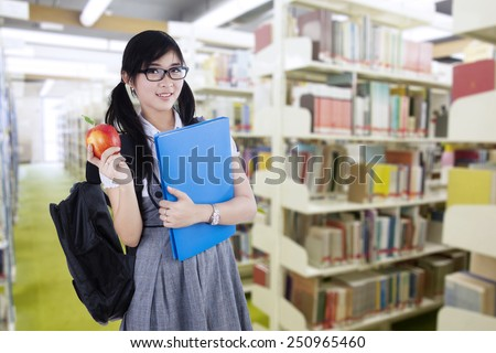 Young attractive female student standing in the library while holding a red apple and folder - stock photo