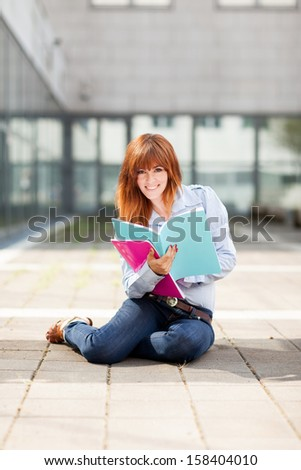 Young attractive female student with notebooks in her hands