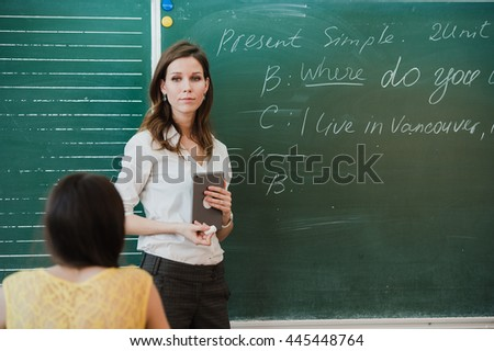 Young attractive female teacher of maths interacting with her young primary school students asking a young girl for an answer