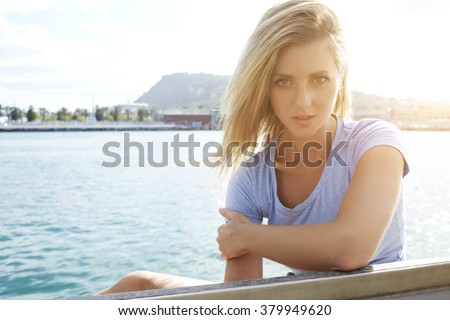 Young attractive female with gorgeous blonde hair posing near sea to create a portfolio for model agency, charming woman with pretty face looking at camera while relaxing outdoors during free time - stock photo