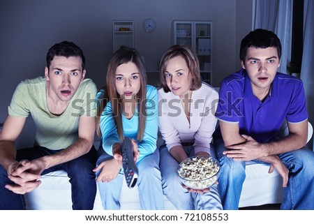 Young attractive friends watch in amazement at the TV