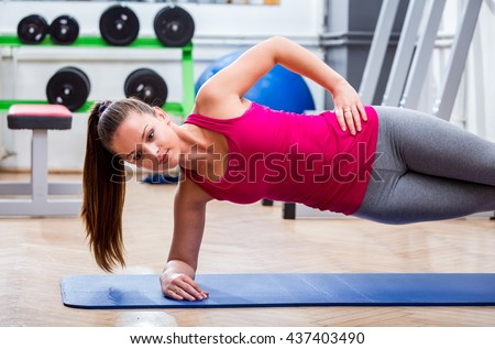 Young, attractive, girl at the gym side planking on the floor in sportswear for better shape, endurance and fitness. - stock photo