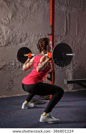 Young attractive girl athlete squats with weights. Sport Club. Fitness club. Healthy lifestyle concept. - stock photo