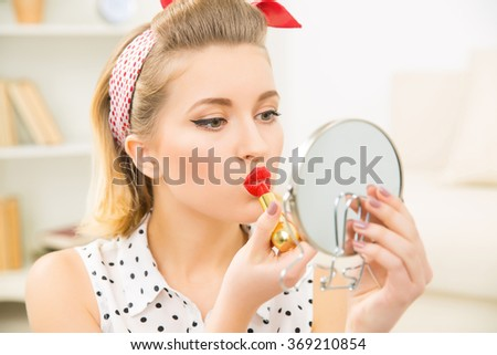 Young attractive girl busy with her make up. - stock photo