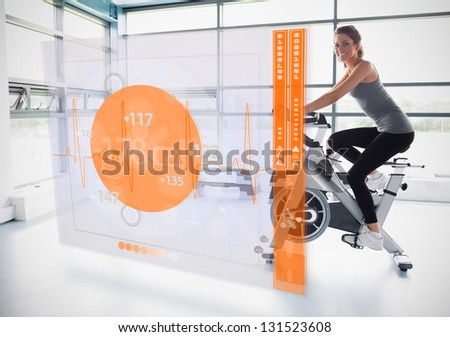 Young attractive girl doing exercise bike with futuristic interface showing calories - stock photo