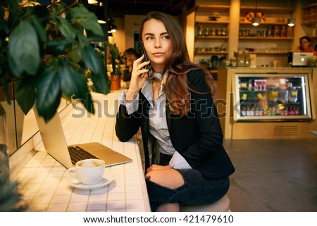young attractive girl freelancer working remotely while sitting at a table in a cafe.young attractive girl talking on the cell phone during lunch break.modern business woman using a laptop computer. - stock photo