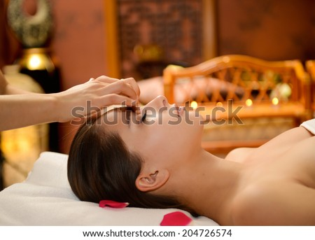 Young attractive girl having facial massage at spa resort