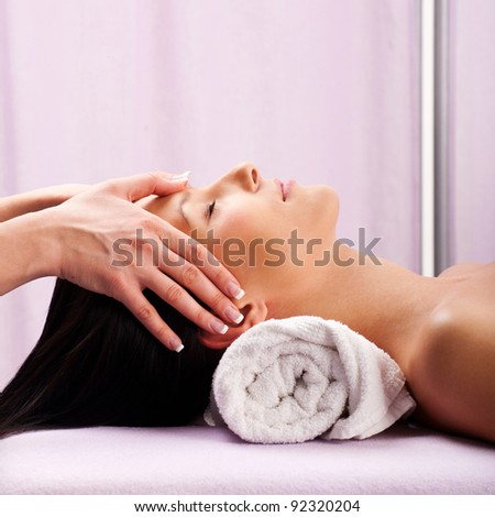 Young attractive girl having head massage at spa resort - stock photo