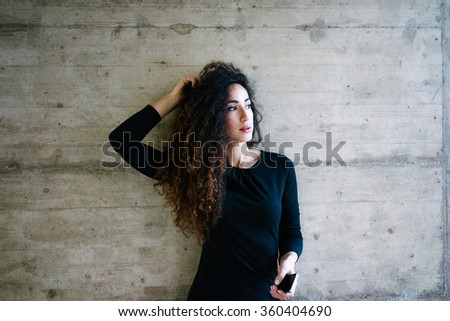 young attractive girl holding smart-phone on the background of concrete wall with blank copy space for your text and design.Beautiful young business woman using a cell phone - stock photo