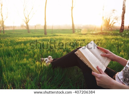 young attractive girl immersed in the world of dreams and fantasy reading a bestseller in the park sitting on the grass in the rays of the setting of the spring sun. girl peep over his shoulder.  - stock photo