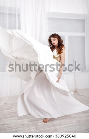 Young attractive girl in a long white dress. Long hair. - stock photo