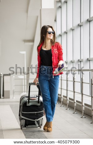 young attractive girl in a red jacket with a suitcase goes on the terminal.  - stock photo