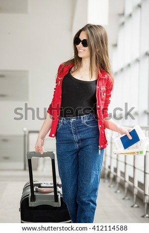 young attractive girl in a red jacket with a suitcase goes on the terminal. In all growth. - stock photo