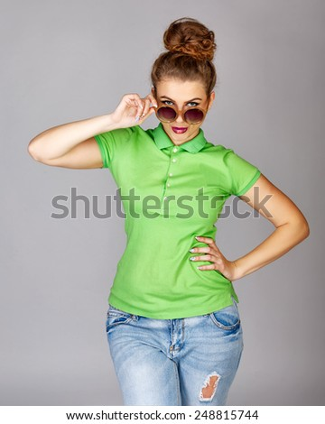 Young attractive girl in a T-shirt, faded jeans and sunglasses shows the emotions of joy and wonder, shot in studio - stock photo