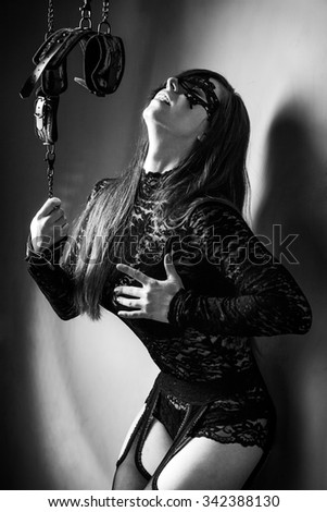 Young attractive girl in bra and lace underwear. Girl hands handcuffed with chains.  The concept of BDSM and bondage.