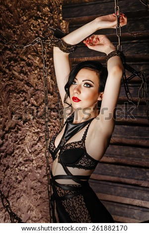 Young attractive girl in bra and lace underwear. The girl raised her hands up, hands handcuffed with chains. The concept of BDSM and bondage. - stock photo