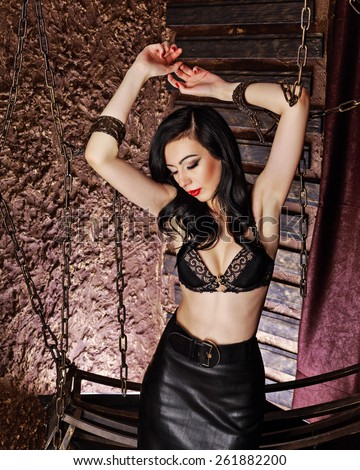 Young attractive girl in bra and leather skirt. The girl raised her hands up, hands handcuffed with chains. Girl's head is omitted and eyes closed. The concept of BDSM and bondage. - stock photo