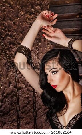 Young attractive girl in bra. The girl raised her hands up, hands handcuffed with chains. Close-up portrait. The concept of BDSM and bondage. - stock photo