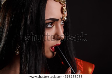 Young attractive girl in elegant black dress smoking narghile hookah. Portrait of a woman smoking hookah. Black background. Studio shot. Beauty portrait of young brunette woman enjoying the hookah. - stock photo