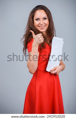 Young attractive girl in red with folders, smiling isolated on grey background. Thumb up gesture - stock photo