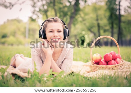 Young attractive girl in summer park wearing headphones - stock photo