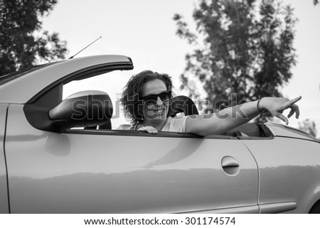 Young attractive girl in the car in white shirt and black glasses, smiling from a car and pointing with her finger. Black and white photo.