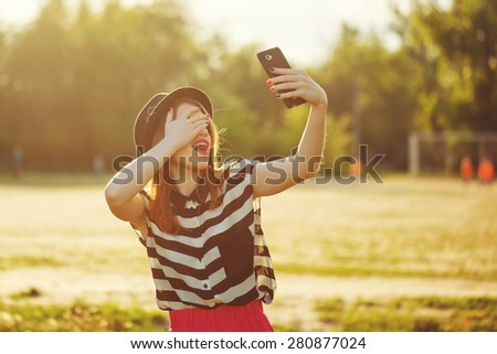 Young attractive girl in the hat does cheerful selfei on a cellphone. The concept of urban street youth fashion. Communication in social networks. - stock photo
