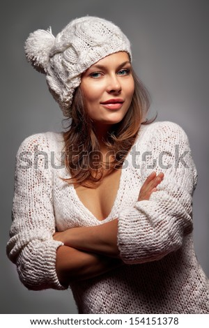 Young attractive girl in white wool and cap over darkness - stock photo