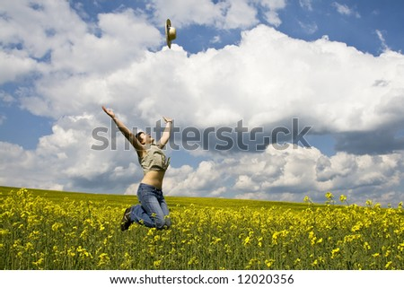 Young attractive girl jumping in rapeseed field and throwing straw hat