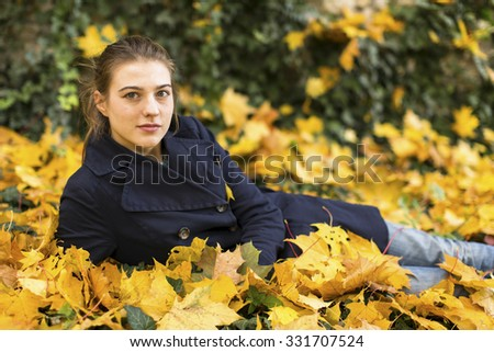 Young attractive girl lying in fallen leaves of autumn. - stock photo