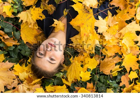 Young attractive girl lying in the autumn yellow leaves. - stock photo