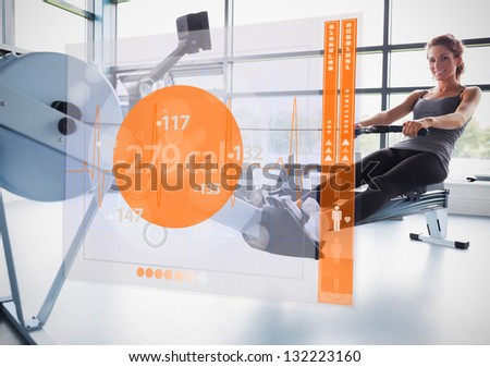 Young attractive girl on rowing machine with futuristic interface showing calories - stock photo
