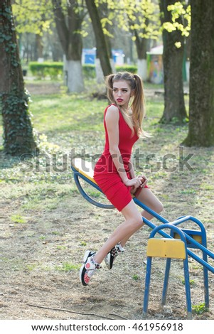 Young attractive girl on swing in red dress with funny hairstyle outdoor