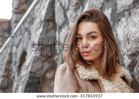 young attractive girl on the background of buildings at sunset