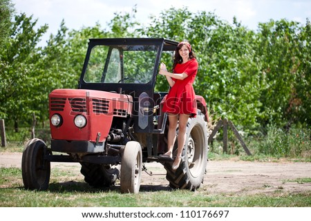 Young attractive girl on tractor, country life