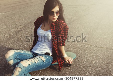 Young Attractive Girl Posing With Skate On Ground. Vintage Effect Fashion Sports Style Photo - stock photo