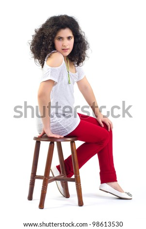 Young attractive girl sitting on a chair isolated on white background
