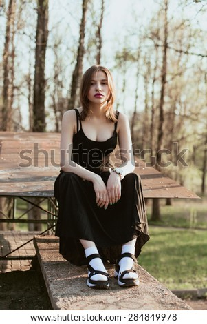 Young attractive girl sitting on the curb. Portrait of pensive girl outdoors - stock photo