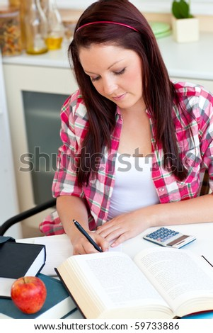 Young attractive girl studying at home in the kitchen
