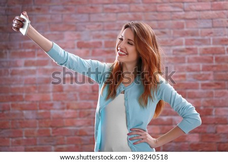 Young attractive girl taking selfie with mobile phone on brick wall background - stock photo